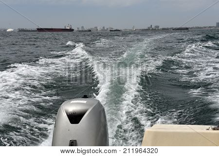 Long Beach California seen in the distance behind a boat wake