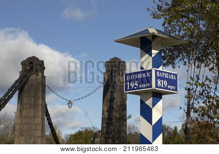 Milepost with names of the cities in Russian and distance in kilometers and with the suspension bridge on a background