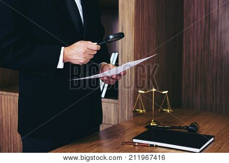 Male lawyer reading legal contract agreement and examining documents with magnifying glass in courtroom.