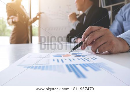 Business woman leader making presentation with her colleagues pointing to the graph on board and business strategy during meeting in modern office.