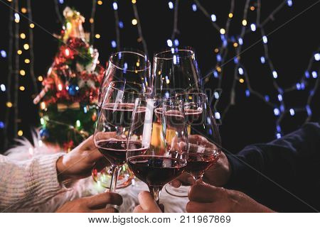 Friends celebrating Christmas or New Year eve party cheering with wine christmas lights decoration background christmas atmosphere.