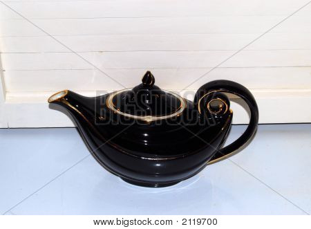 old black antique teapot sitting on a hoosier poster