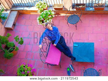 Handsome Caucasian man in early fifties relaxing on Italian patio covered in red terracotta tiles smiling and looking up towards camera