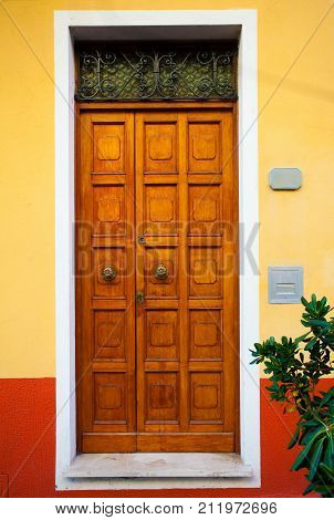 Beautiful antique rustic wood door of Italian home with many wooden panels and yellow and orange front wall.