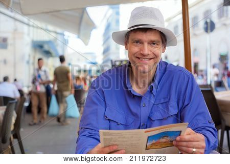Handsome Caucasian man in early fifties sitting at outdoor cafe in Italy or Europe ready to order from menu.