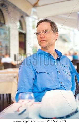 Handsome Caucasian man in early fifties sitting at outdoor cafe or restaurant in Italy France or Europe.