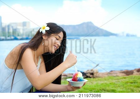Smiling biracial Thai Caucasian teen or young woman at Magic Lagoon eating shave ice. Waikiki and Diamond Head in background.