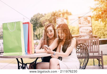 Two Asian Woman Sitting At Store Cafe With Happy Watching Smartphone At Shopping Mall Center.