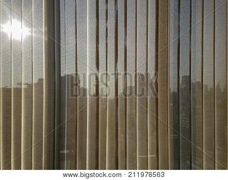 beige brown color semi transparent vertical blinds with blurred afternoon sun and business district buildings seen trhough in the background. the vertical blinds help prevent heat and ultraviolet.