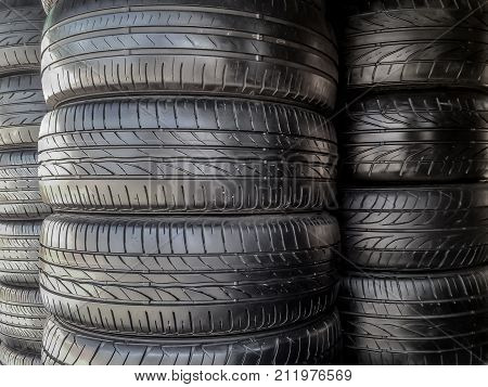 shiny black recapped car tires stack. they are inspected and repair and good to be used in lower cost than new tires.