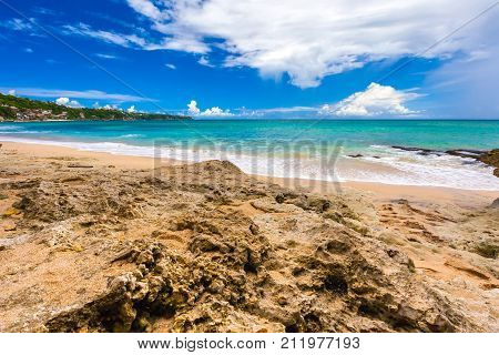 Stone rock yellow on the coast of the azure sea against the backdrop of the coastline and a bright colorful sky with white clouds. Dreamland Beach New, South Kuta, Bali, Indonesia.