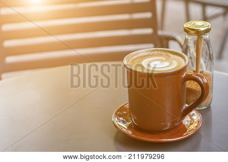 Coffee cup on black metal table in coffee shop with brown sugar bottle and sunlight background. Hot latte coffee. Hot coffee.