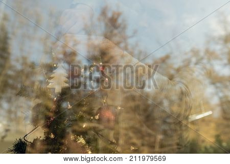 Man in casual clothes decorating Christmas tree visible behind the window with reflection and copy space.