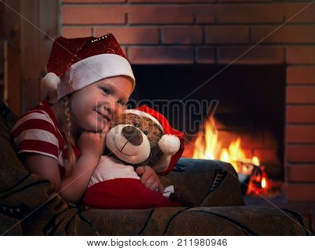A happy girl and a plush bear. Evening at home a comfortable armchair and fireplace