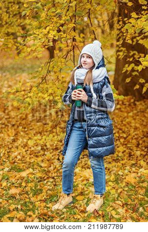 cute teenager girl in a white hat and volumetric scarf holding a thermos with tea in an autumn park