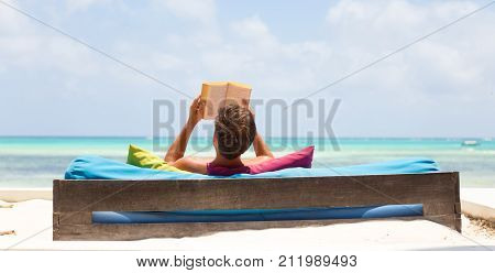 Relaxed man reading book in luxury lounger enjoying summer vacations on beautiful beach. Guy feeling free, relaxed and happy. Concept of vacations, freedom, happiness, enjoyment and well being.