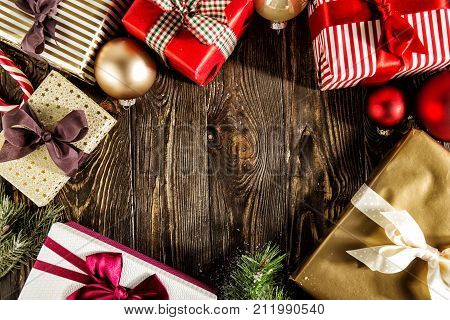 Presents decorated with ribbons arranged together on wood with Christmas adornments. poster