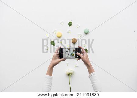 Hands holding a smart-phone capture a macaroon