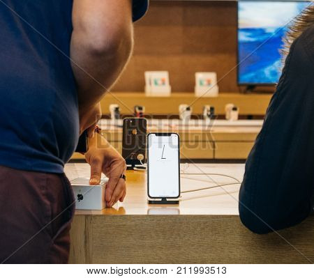 STRASBOURG FRANCE - NOV 3 2017: Apple Genius selling scanning the latest Apple iPhone X to first customers in France at Apple Store
