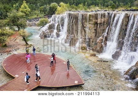 Lijiang, Yunnan, China - September 23, 2017: Tourists On The White Water River Waterfall Viewing Pla