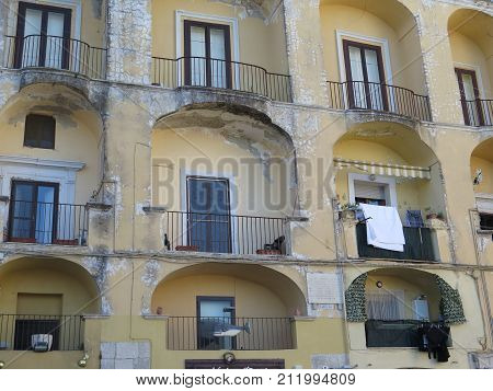 Delapidated balcony arches on old building in Gaeta historic part Italy