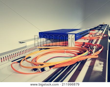 Fiber optic cables running from a switch. Information technology in industry.