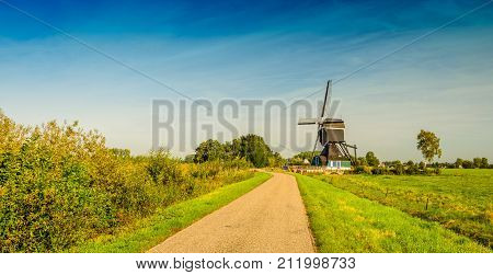 Picturesque panoramic image of a Dutch country road with a wooden hollow post polder mill from 1762 restored in 1953. The mill is now a national monument and no longer in use as a polder mill. poster