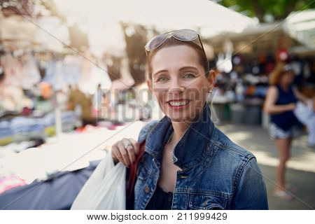 Happy attractive stylish woman shopping at an outdoor market standing looking at the camera with a wide warm friendly smile