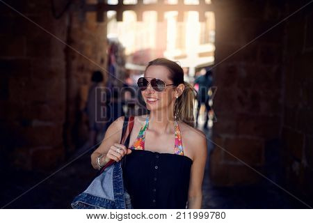 Attractive trendy woman wearing sunglasses and carrying a large handbag over her shoulder shopping in town looking to the side with a smile