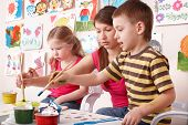 Children painting with teacher in art class. Child care. poster