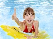 Children sitting on inflatable ring in swimming pool. poster