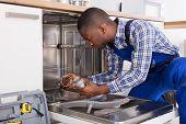 Young African Repairman Repairing Dishwasher In Kitchen poster