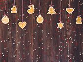 Gingerbread cookies on rope for christmas tree decoration new year on wooden table. Festive sweet pastry delicious food. Various cookies gingerbread star heart christmas ball sock Santa Claus mitten poster