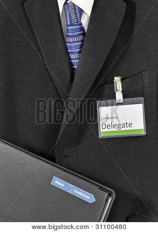 Closeup on male business suit with conference folder and delegate name badge. The creative design on the folder  has been falsified poster