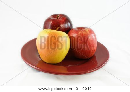Three Apples On A Red Plate