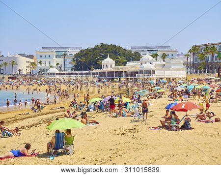 Cadiz, Spain - June 23, 2019. People Enjoying A Sunbathing In La Caleta Beach. View From Paseo Ferna