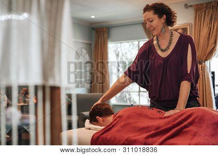 Woman spiritual healer preforming reiki healing using crystals. poster