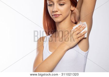 Woman wiping the armpit with wet wipes, perspiration, sweat remove