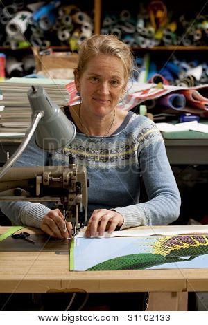 Middle-aged caucasian seamstress working in her studio