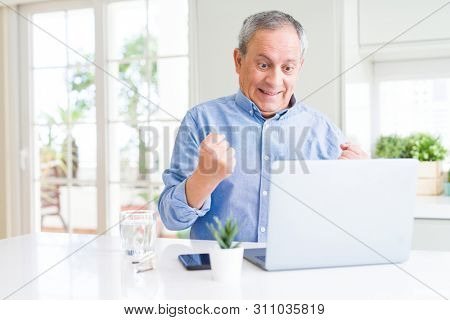 Handsome senior man using computer laptop working on internet screaming proud and celebrating victory and success very excited, cheering emotion