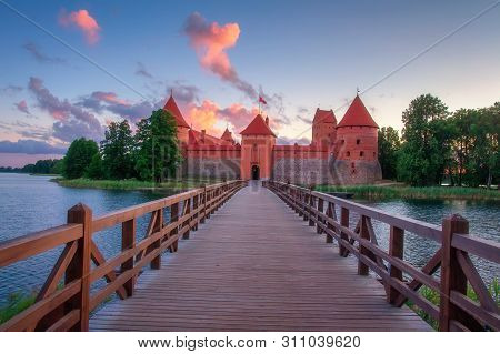Trakai Castle At Dawn, Lithuania. Pink Clouds Over Trakai Castle On Island In The Morning Sunrise. S
