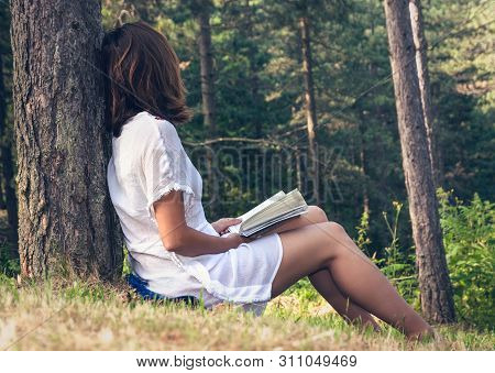 Beautiful Woman Reading Book In Nature In Vacation. Beautiful Woman Reading Book In Nature. Happy Be