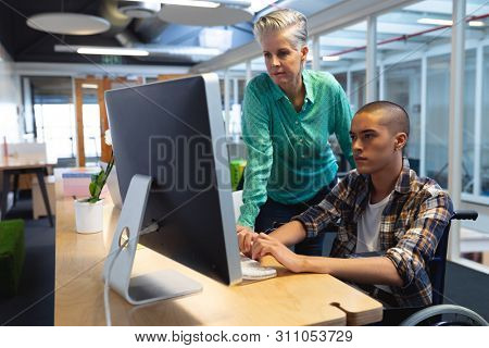 Side view of diverse executives working together on computer at desk in office. This is a casual creative start-up business office for a diverse team