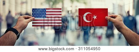 Two Hands Holding Different Flags, Us Vs Turkey On Politics Arena Over Crowded Street Background. Di