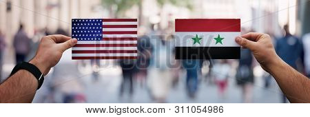 Two Hands Holding Different Flags, Usa Vs Syria On Politics Arena Over Crowded Street Background. Di