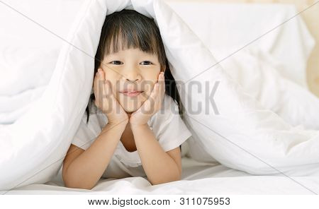Cute Little Girl Hiding In Bed Under A White Blanket Or Coverlet On White Bed