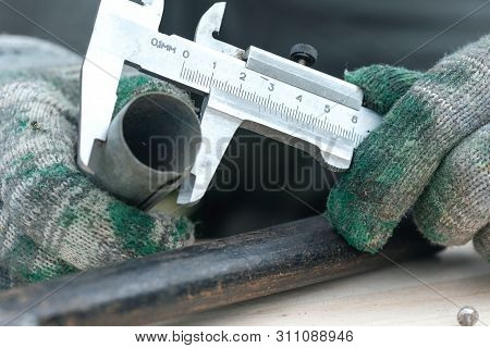 Worker is holding in hands a metal part and is measuring a diameter by a calipers. poster
