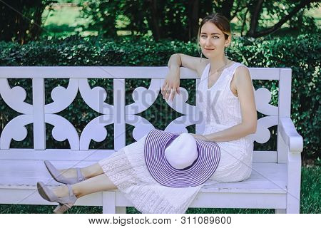 Young Beautiful Girl In A White Dress Sitting On A White Bench In The Summer Park