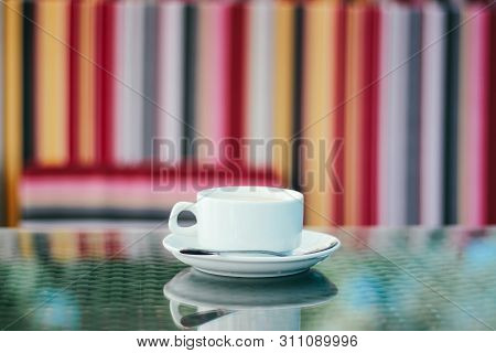 White Cup Of Coffee With A Saucer On The Table Close-up In An Outdoor Cafe On The Street