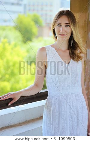 Young Beautiful Girl In A White Dress Close-up On The Aqueduct Bridge Background